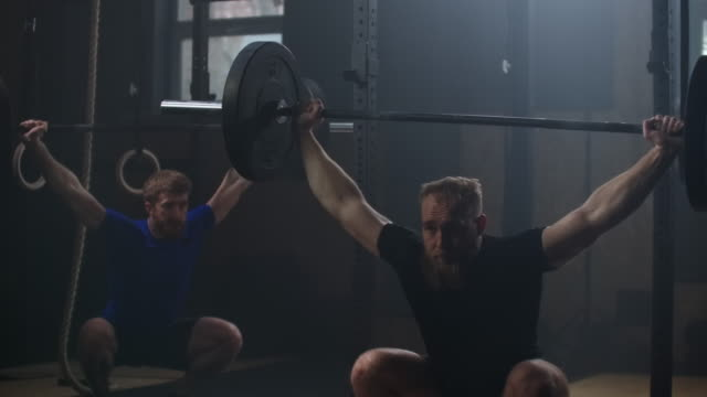 vídeos de stock e filmes b-roll de two strong man doing weightlifting training together at the gym. medium shot slow motion pan men exercising in gym with exercise equipments: overhead squats, plate lunges, medicine ball, olympic rings - agachar se