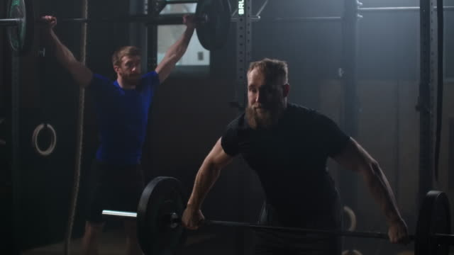 Two strong man doing weightlifting training together at the gym. Medium shot slow motion pan men exercising in gym with exercise equipments: Overhead squats, plate lunges, medicine ball, olympic rings