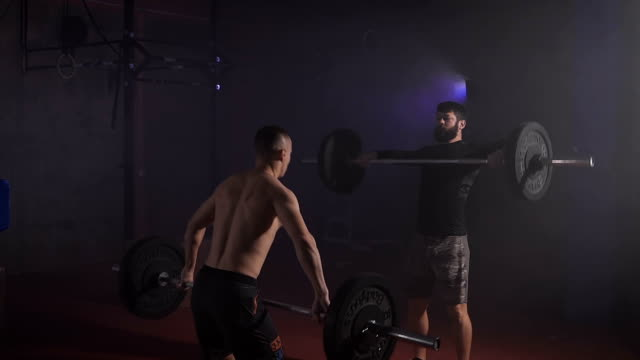 Two strong men doing weightlifting with barbell at the gym simultaniously video