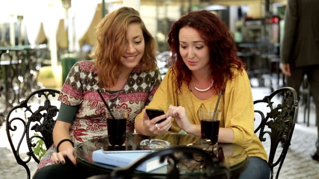 Two student girls in cafe Two student girls having good time in cafe park bench stock videos & royalty-free footage