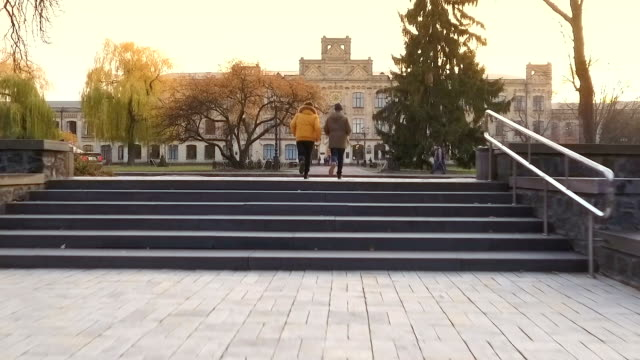 Two students are late to the university Two students are late to the university on lectures. Two guys are running to the entrance of campus through the autumn park and road. Camera slowly moves up and follows by the people. campus stock videos & royalty-free footage