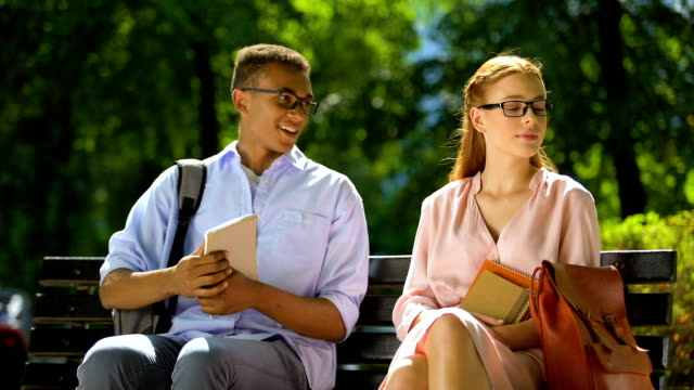 Two students making acquaintance sitting on bench in park, first impressions
