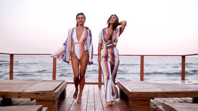 2 つのスタイリッシュな白人日焼けした女性は似たようなスタイルの服は風の強い日に屋外木製床で歩きます。海辺、フロント ビュー - スタイリッシュ点の映像素材/bロール