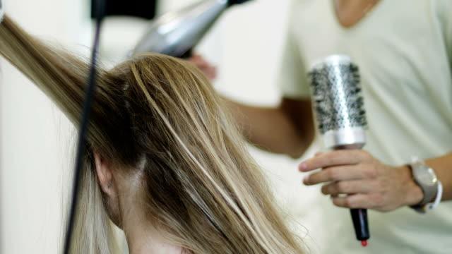 Zwei Stylisten der Friseur trocknen die lange Haare von einem jungen Modell mit einem Fön – Video