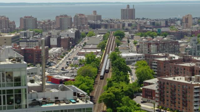 vidéos et rushes de deux trains de métro à cheval à travers le quartier résidentiel de brooklyn, new york. drone vidéo avec le mouvement de la caméra panoramique. - hlm
