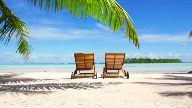 フランス領ポリネシアの熱帯のビーチの 2 つのサンベッド - リゾート点の映像素材/bロール