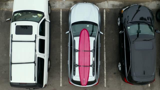stockvideo's en b-roll-footage met twee surfers lossen surfplank uit imperiaal-luchtfoto drone shot - parking