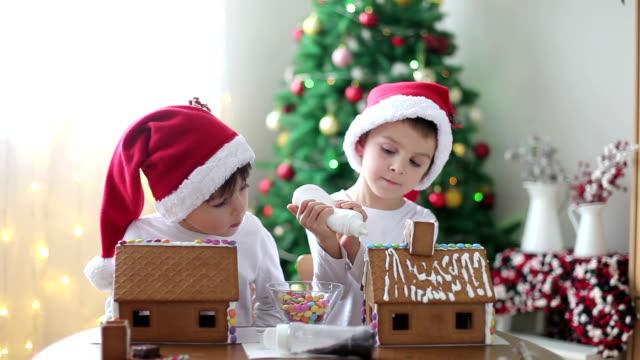 zwei niedlichen jungen, brüder, und lebkuchen cookies house - lebkuchenhaus stock-videos und b-roll-filmmaterial