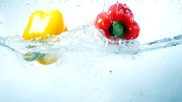 Two sweet peppers fall into water together. video
