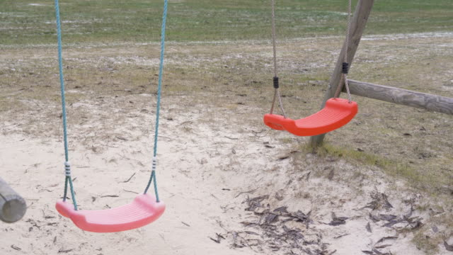 Two swings on the playground swaying on the wind Two swings on the playground swaying on the wind with the white sand on the ground outdoor play equipment stock videos & royalty-free footage