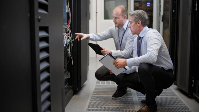 DS Two technicians squatting in the server room discussing connections video