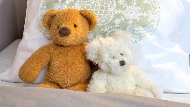 stockvideo's en b-roll-footage met twee teddyberen zittend op het bed in de kamer - comfortabel