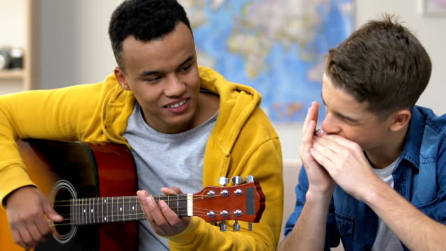 Two teen friends enjoy playing guitar and harmonica together, musical hobby