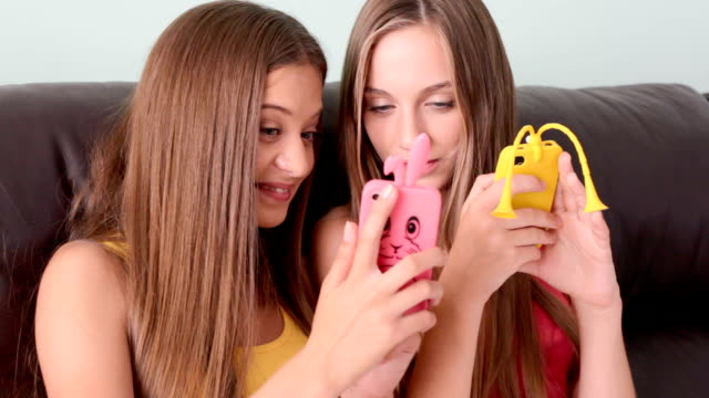 Two teenage girls having fun with phones video