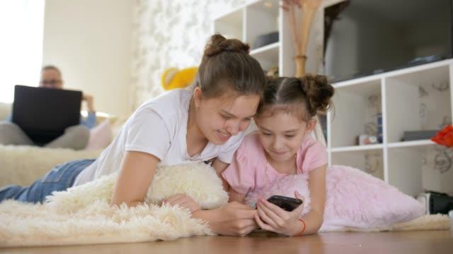 vídeos y material grabado en eventos de stock de dos adolescentes acostadas en el suelo en la sala de estar y ver algo interesante en su teléfono inteligente. - hermana