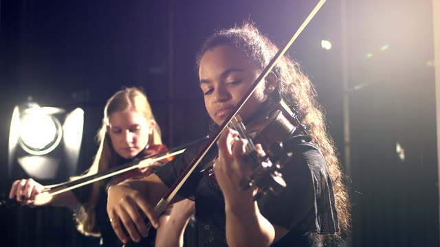 Two teenage girls playing violin in concert Two multi-ethnic teenage girls playing the violin in a concert performance. The focus is on the 15 year old mixed race musician in the foreground. performer stock videos & royalty-free footage