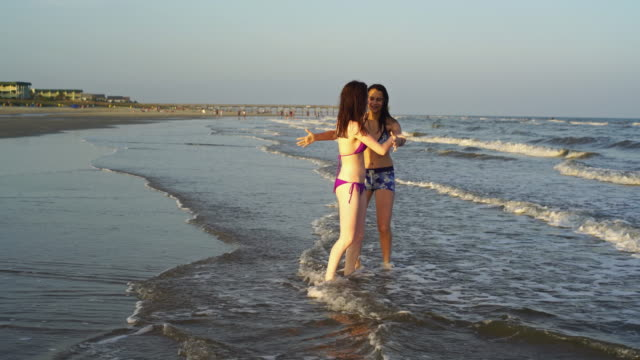 Two teenager girls runs and plays in the water at the ocean beach video