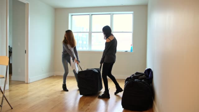 Two teenager girls, sisters, moving packages in the living room of the new empty house video