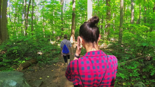 vídeos de stock e filmes b-roll de two teenager girls walking through the forest - amizade feminina