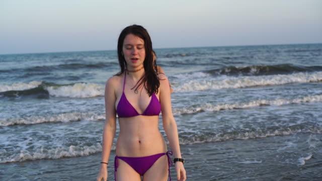 vídeos de stock, filmes e b-roll de duas meninas adolescentes passeios fora da água na praia - 16 17 anos