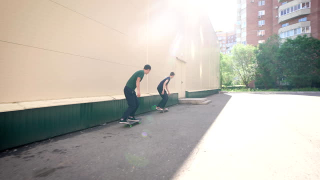 Two teenagers are skating outdoors in sunny summer day. Young urban people are jumping over the porch with boards. Group of extreme sportsmen are making sport tricks with skateboard video