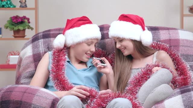 Two teenagers in Santa Claus hats and glistening talking speakerphone video