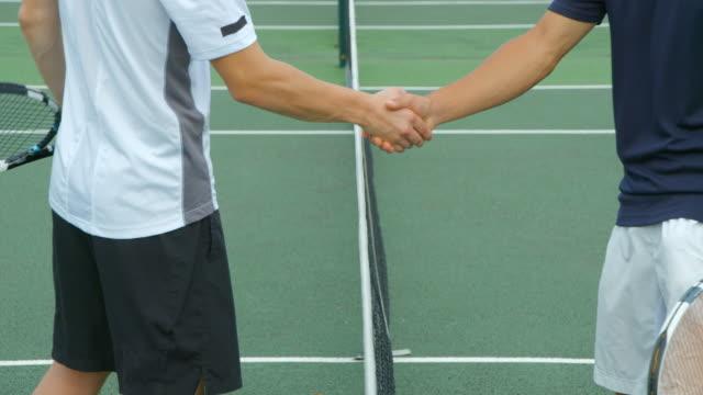 Zwei Tennis-Spieler schütteln Hände über das Netz – Video