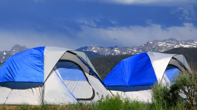 Two tents during the day as storm passes in the distance - 4k time lapse video