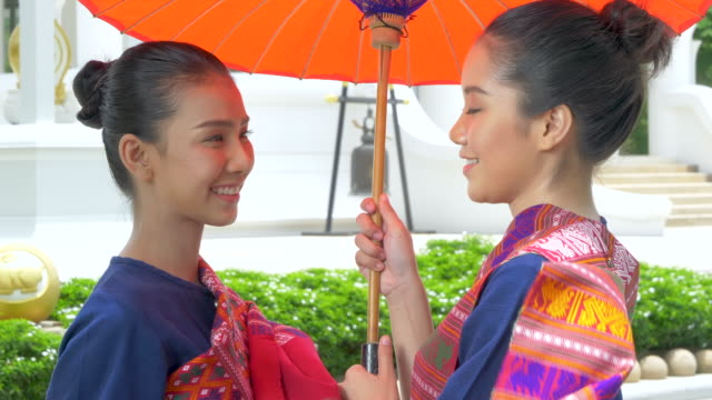 Two Thai young woman wearing Thailand national dress suit holding red umbrella. Welcome to Thailand concept.