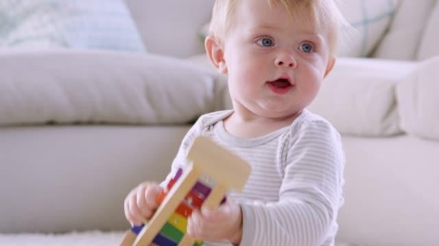 stockvideo's en b-roll-footage met twee peuter jongens spelen op de vloer in de zitkamer - baby toy