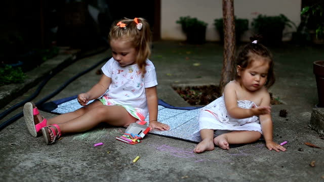 Two toddlers drawing outside with color chalks video