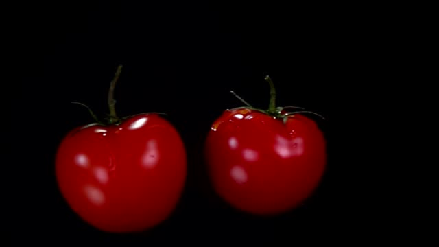 Two tomatoes are flying towards each other, colliding on the black background - video