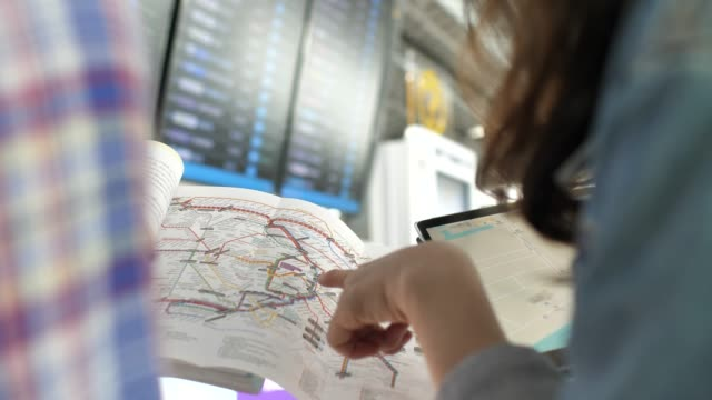 Two tourist looking on city map with Digital tablet at Airport video