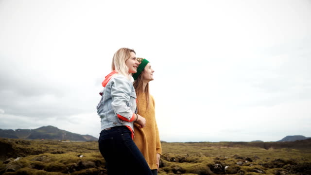 Two tourists female standing on the lava field in Iceland and pointing with finger on something. Happy woman talking