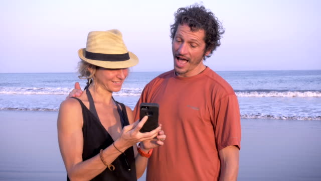 Two tourists look at photos on phone while standing on the beach