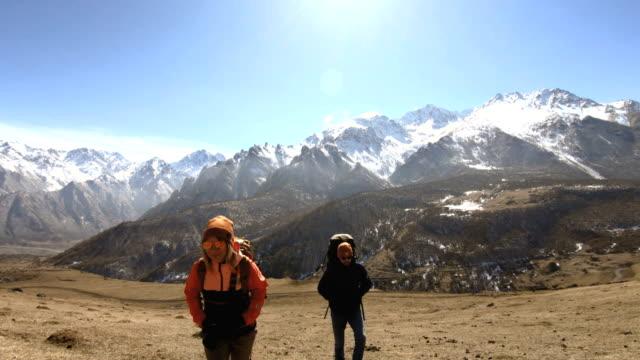 два туриста фотографы бородатый мужчина и девушка блондинка с рюкзаками в шляпах и солнцезащитных очках идут вверх по склону по желтой тра� - турист с рюкзаком стоковые видео и кадры b-roll