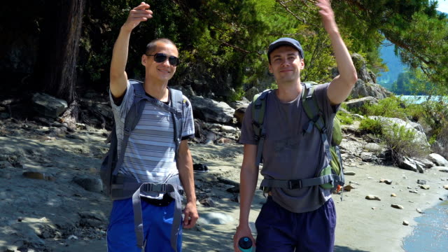 vídeos de stock, filmes e b-roll de dois turistas acenando as mãos para outros turistas. - primeira comunhão