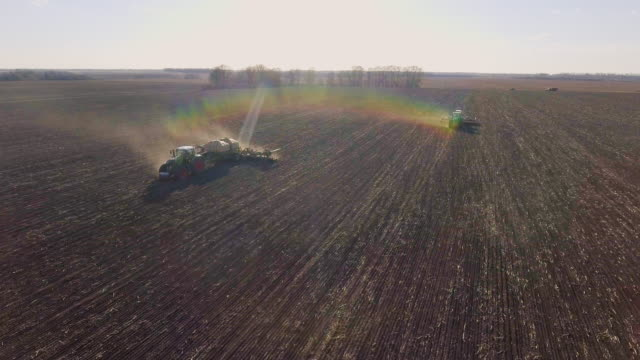 Two tractors sow the field in the spring. Shooting before sunset, beautiful highlights and rainbow effect video