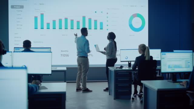 två handlare som har ett möte i ett modernt övervakningskontor med analytics-flöde på en stor digital skärm. övervakningsrum med mäklare och specialister ekonomi sitta framför datorer. kollegor prata. - server room bildbanksvideor och videomaterial från bakom kulisserna