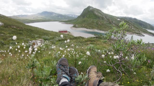 Two travelers sitting on the hill above a Norwegian fjord.