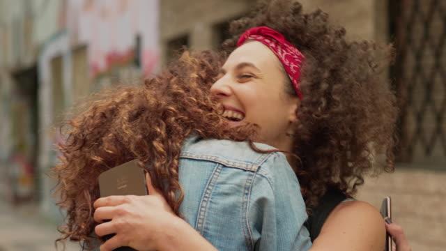 två resande vänner träffas och kramar varandra i staden - välkommen bildbanksvideor och videomaterial från bakom kulisserna