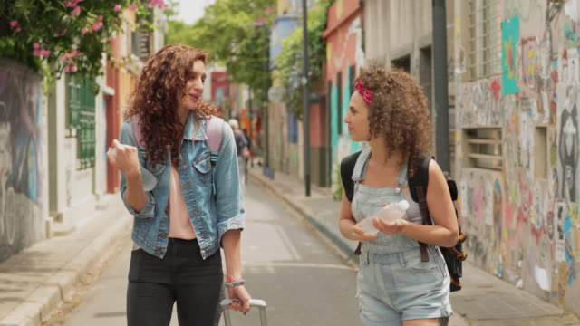 two traveling friends walking down a city street together - palermo città video stock e b–roll