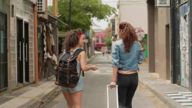 due amici in viaggio che camminano lungo una strada della città insieme - argentina america del sud video stock e b–roll