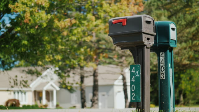Two typical American outdoors mailboxes. Clear sunny day video