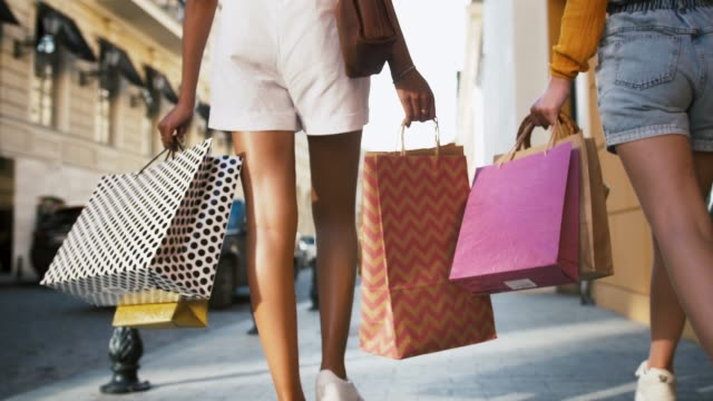 two unknown young females in shorts and sneakers are walking down the city street with colorful shopping packages in hands. close up, slow motion - pantaloncini video stock e b–roll