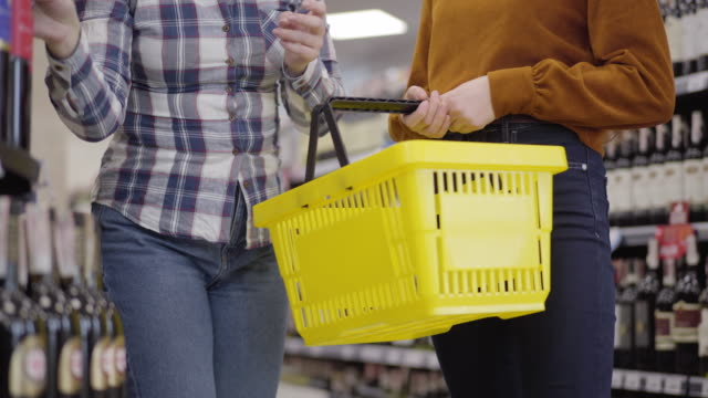 Two unrecognizable Caucasian women standing between shelves with alcohol in supermarket and putting bottles of red and white wine into shopping basket. Adult girls buying beverage in shop. Lifestyle.