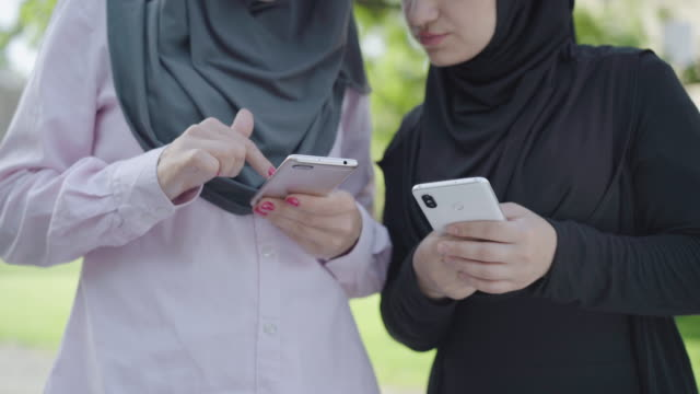 two unrecognizable muslim women using smartphones on sunny day outdoors. confident female friends in hijabs surfing internet. modern ladies using social media. lifestyle concept. - abbigliamento modesto video stock e b–roll