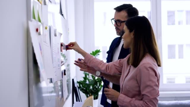 två ux-specialister diskuterar hem sida, appdesign - whiteboardtavla bildbanksvideor och videomaterial från bakom kulisserna