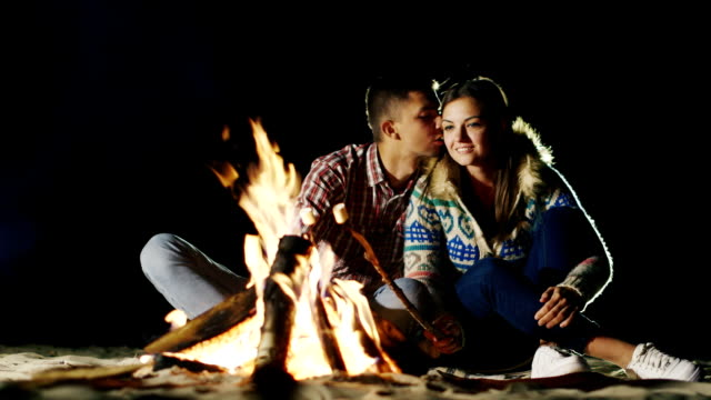 Two video : Man and woman relaxing evening around the campfire, roast marshmallows on sticks fire - video