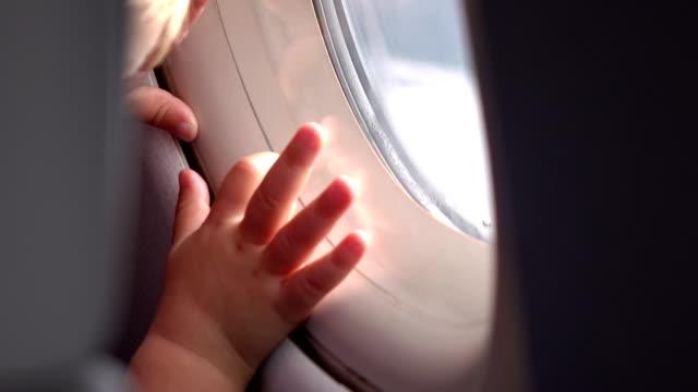 två videor av barn tittar genom fönstret flygplan i 4k - människohuvud bildbanksvideor och videomaterial från bakom kulisserna